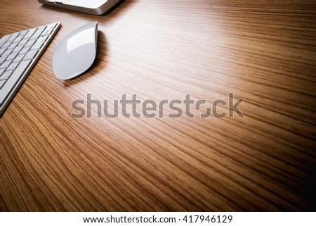 Side view of mouse, keyboard and laptop on wooden desk with copy space.
