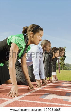 Side view of multi ethnic business people at starting line on race track - stock photo