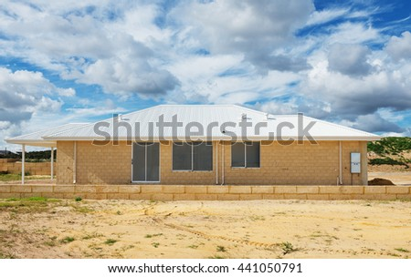 Side view of new suburban home currently under construction against cloudy sky - stock photo