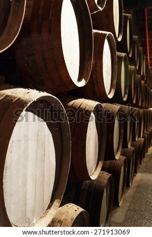 Side view of oak barrels stacked in the old cellar with aging Port wine from the vineyards Douro Valley in Portugal. Product of organic farming. - stock photo