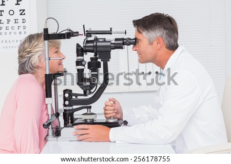 Side view of optician examining senior patient through slit lamp in clinic - stock photo