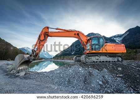 side view of orange shovel digger on gravel at lake and blue sky - stock photo
