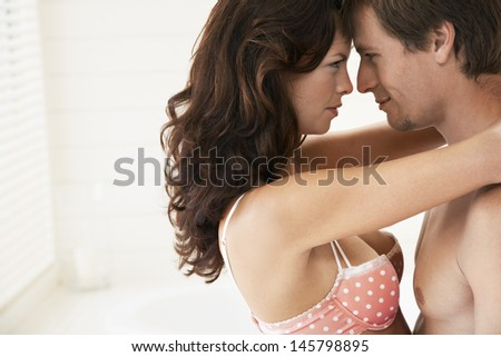 Side view of passionate young couple embracing in bedroom - stock photo