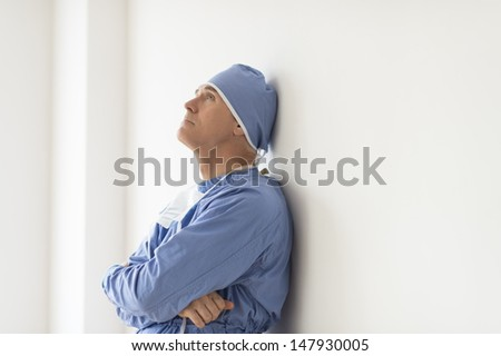 Side view of pensive male surgeon with arms crossed leaning on wall in hospital