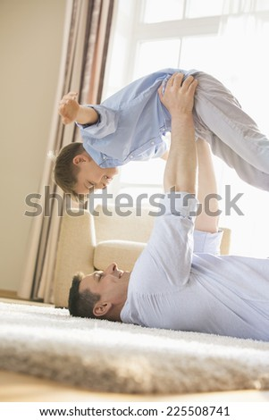 Side view of playful father picking up son while lying on floor at home - stock photo