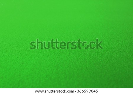Side view of poker table surface of green fabric - stock photo
