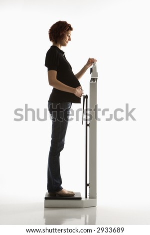 Side view of pregnant Caucasian mid-adult woman reading her weight on scale. - stock photo