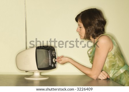 Side view of pretty Caucasian mid-adult woman sitting at 50's retro dinette set turning old televsion knob. - stock photo