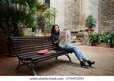 Side view of pretty young female tourist studying a map sitting on wooden bench during her travel in Barcelona - stock photo