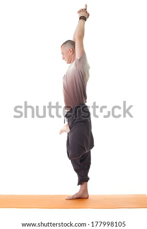 Side view of relaxed yoga man standing on one leg