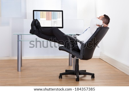 Side view of relaxed young businessman sitting feet up at office desk - stock photo