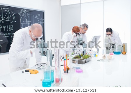 side-view of researchers in chemistry lab analyzing under microscope on a worktable around lab tools and colorful liquids and a blackboard with formulas on the background
