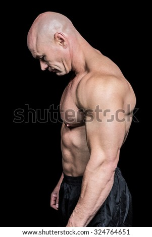 Side view of sad muscular man looking down against black background - stock photo