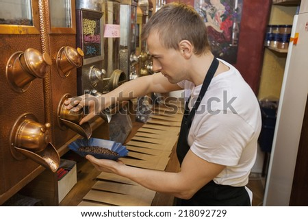 Side view of salesperson dispensing coffee beans into bowl at store - stock photo