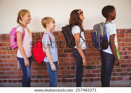 Side view of school kids standing in school corridor - stock photo