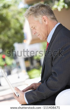 Side view of senior business man working on laptop