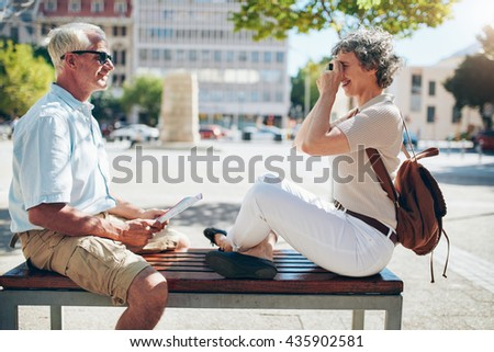 Side view of senior man sitting outdoors on a bench and woman taking his pictures with digital camera. Senior couple having fun on their vacation. - stock photo