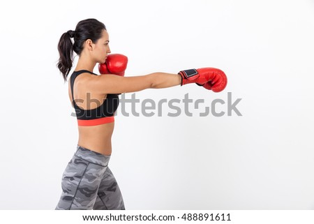Side view of serious boxer girl in sweatpant and sport bra making a punch. Concept of boxing and martial arts. Mock up