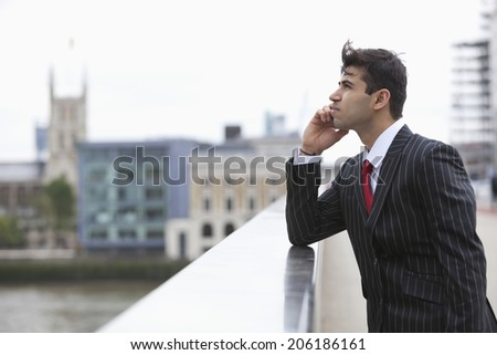 Side view of serious Indian businessman on call outdoors - stock photo