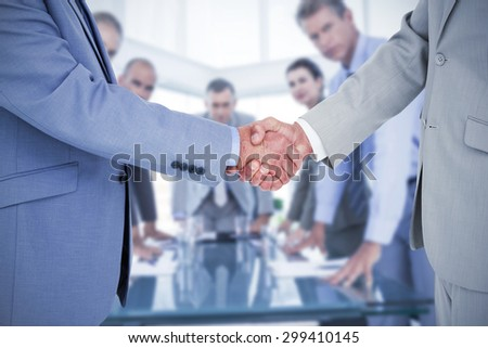 Side view of shaking hands against business colleagues discussing about work - stock photo
