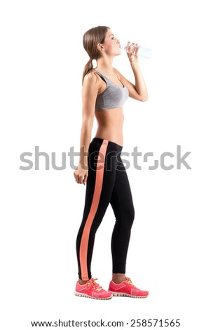 Side view of slim fitness woman drinking water. Full body length portrait isolated over white background. - stock photo