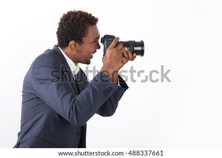 Side view of smiling African American photographer in gray suit. Concept of professional photoshooting. Mock up