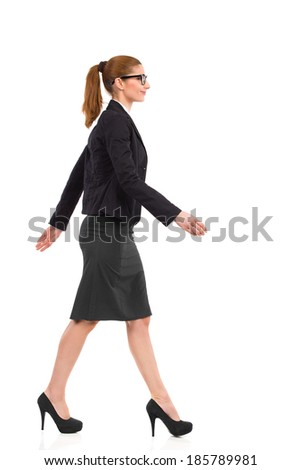 Side view of smiling and walking businesswoman in black suit, skirt and high heels. Full length studio shot isolated on white. - stock photo