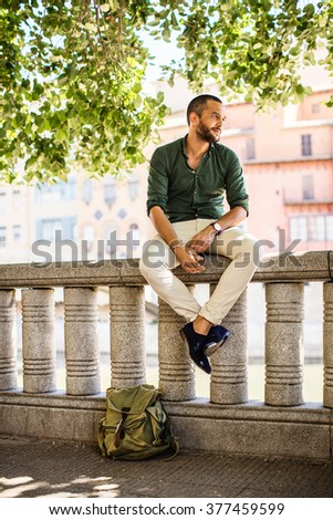 Side view of smiling bearded man sitting on fence under trees.Summer time - stock photo