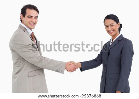 Side view of smiling business partners shaking hands against a white background