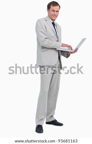 Side view of smiling businessman using his laptop against a white background