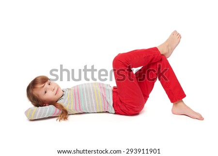 Side view of smiling child girl lying on her back on the floor with crossed legs looking at camera, over white background  - stock photo