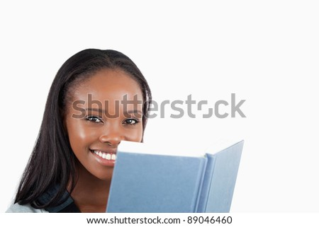 Side view of smiling woman reading a book against a white background - stock photo