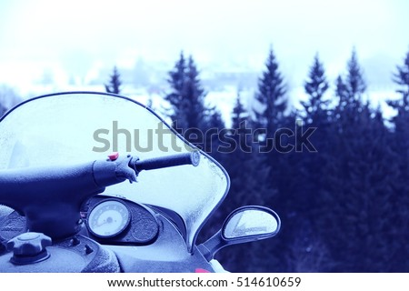 Side view of Snowmobile in winter mountains with forest