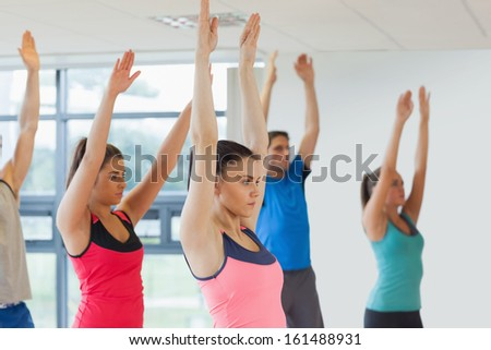 Side view of sporty people raising hands at yoga class in fitness studio