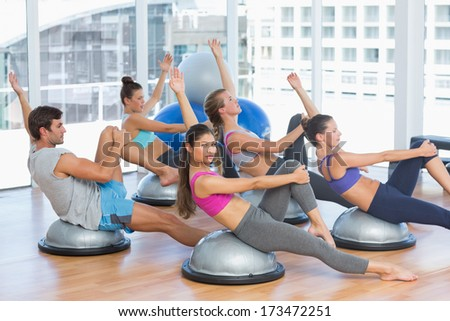 side view of sporty people stretching hands at yoga class in fitness studio
