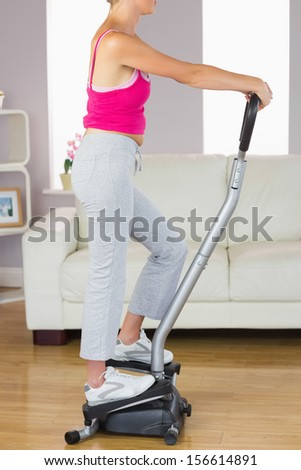 Side view of sporty woman training on step machine in bright living room