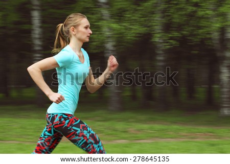 Side view of sporty young woman running in park. Health conscious concept with copy space - stock photo
