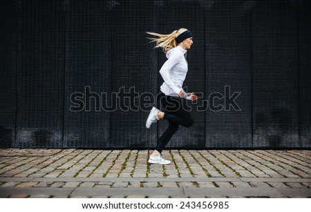Side view of sporty young woman running on sidewalk in morning. Health conscious concept with copy space. - stock photo
