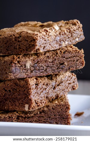 Side view of stack of homemade double chocolate chunk brownies sitting on white plate - stock photo