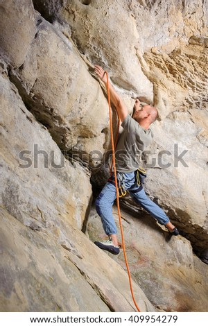 Side view of strong male lead climber climbing big boulder in nature. Man is holding climbing rope and searching for the next grip. Summer time. Climbing equipment - stock photo