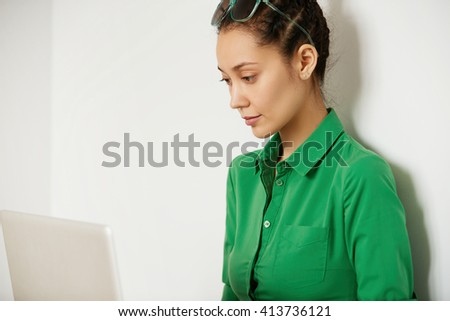 Side view of student girl in green shirt working on course paper while sitting in front of computer, looking at the screen against white studio background with copy space for your promotional content - stock photo