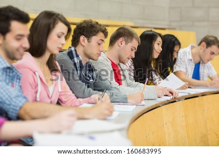 Side view of students writing notes in a row at the college lecture hall - stock photo