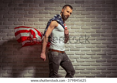 Side view of stylish man with beard covered with American flag like superhero, looking at camera, standing against brick wall - stock photo