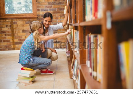 Side view of teacher and little girl selecting book in the library - stock photo