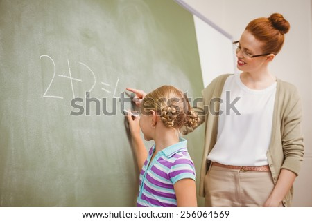 Side view of teacher assisting little girl to write on blackboard in the classroom - stock photo
