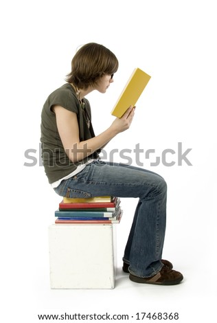 side view of teenage girl sitting on stack of books, reading. - stock photo