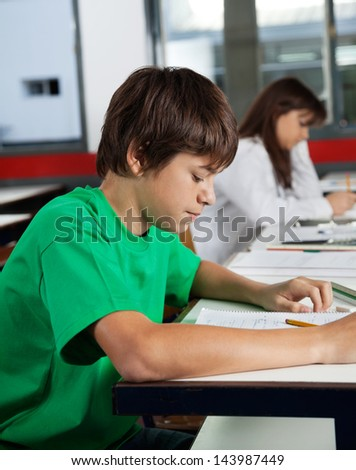 Side view of teenage schoolboy studying at desk in classroom
