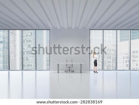 Side view of the blonde employee who looks out the window in New York's panoramic office. A concept of the modern workplace. - stock photo