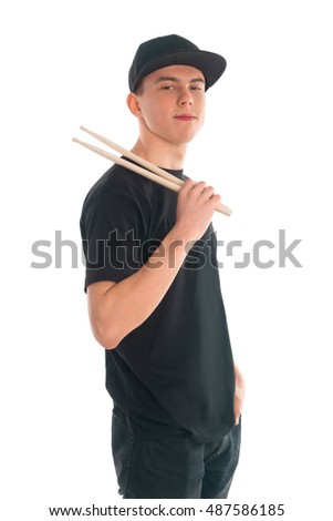 Side view of the boy posing with drumsticks in a black t-shirt and a cap.
