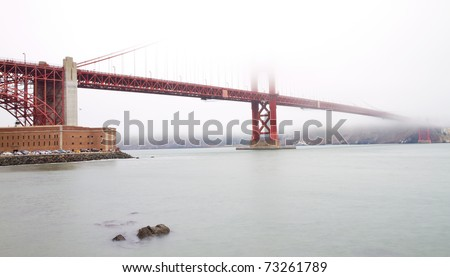 Side view of The Golden Gate Bridge of San Francisco over the mist (long exposure) - stock photo